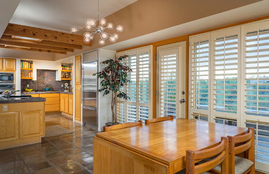 dining-area-into-kitchen-floor-to-ceiling-windows-and-access-to-sunset-patio