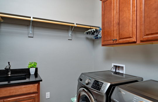 Laundry With Cabinets and Granite Topped Sink