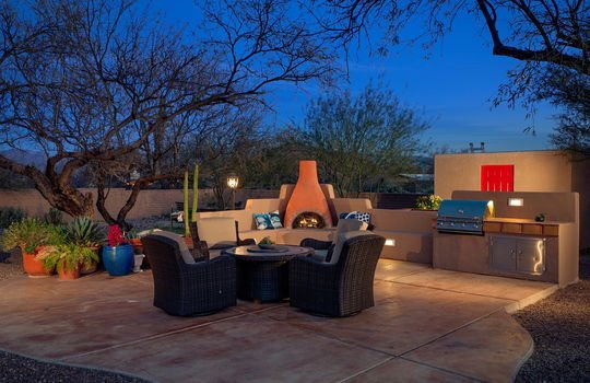 Outdoor Space With Fireplace and BBQ at Twilight