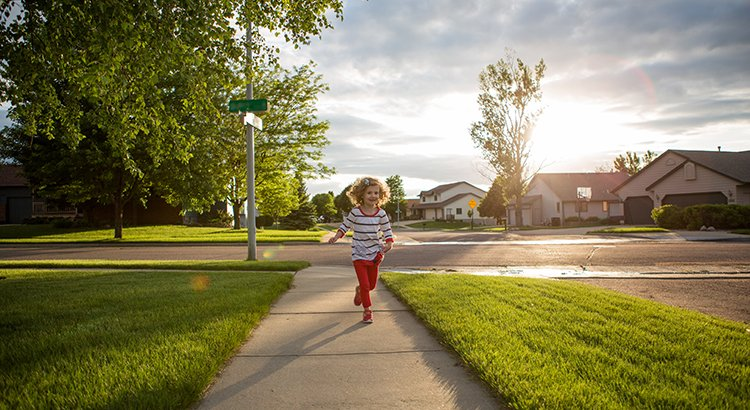 Little Girl with curls running down sidewalk