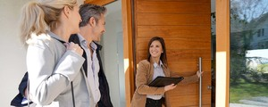 Realtor opening the front door of house for a man and woman