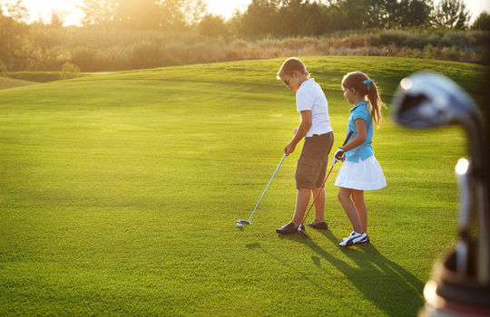 Casual kids at a golf field holding golf clubs