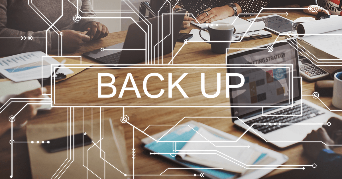 "Image of wooden table top with paperwork and laptops. Copy over image says ""Back Up"""