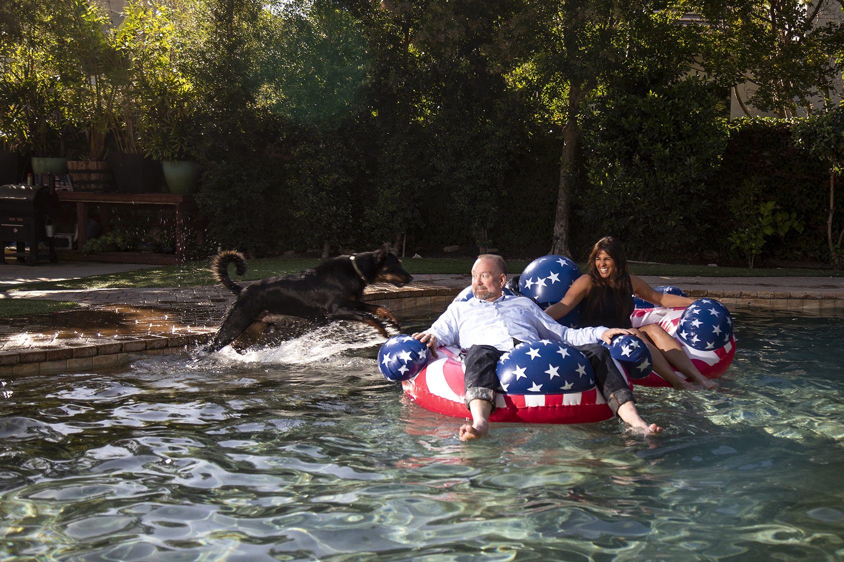 Michele Harrington with her husband and dog in their backyard pool, playing