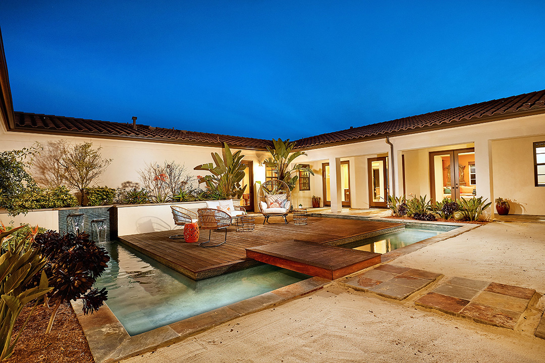 Zen courtyard with teak deck over water feature, and stone pathway in the sand.