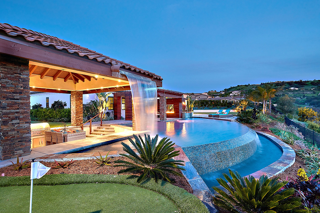 Side view of backyard with putting green, waterfall edge on infinity pool, covered patio with sunken entertaining area and rooftop waterfall and golf course views