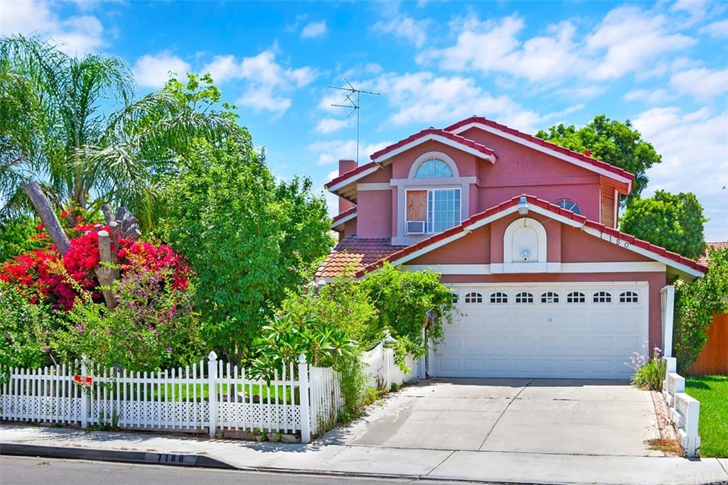 Home exterior with lush front yard, white picket fence, driveway and attached garage.