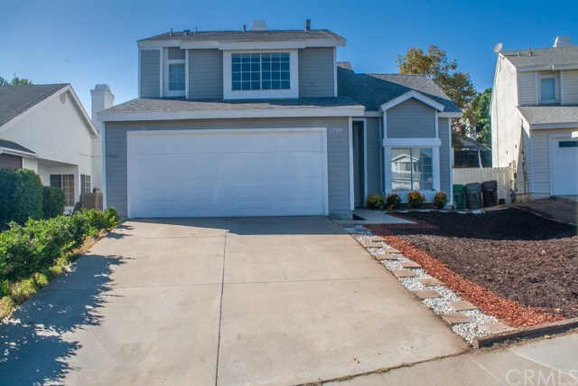 Blue home exterior with driveway and attached garage.