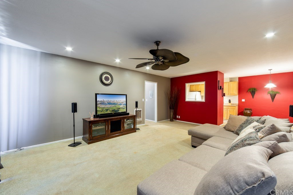 Living room with TV stand, ceiling fan, red accent wall, and couch.