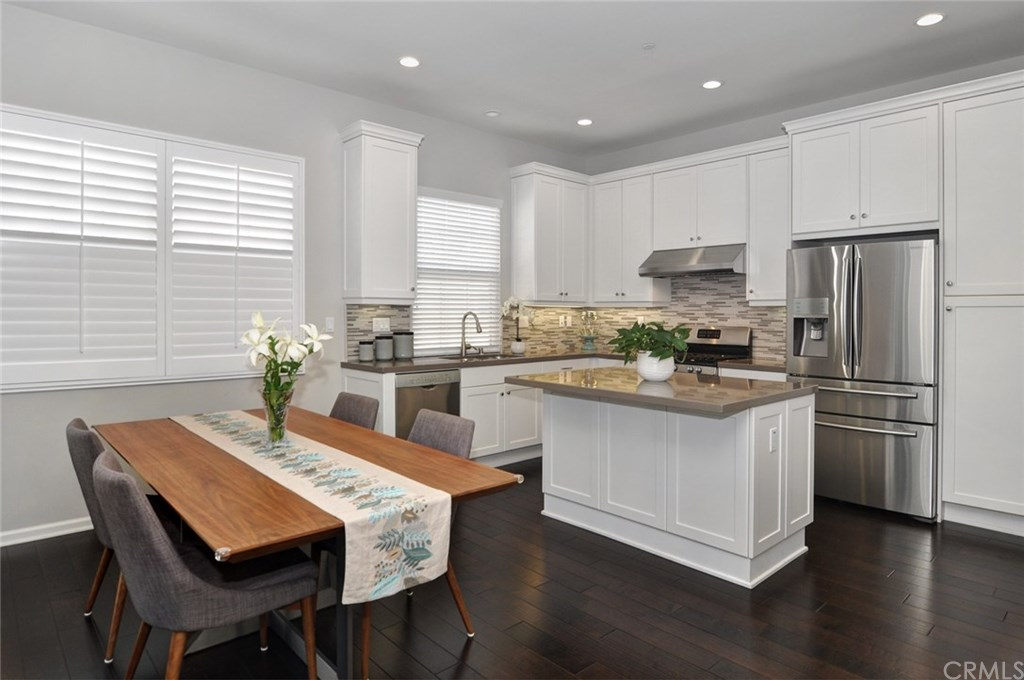 Kitchen and open dining area with stainless steel appliances, large center island and white cabinets.