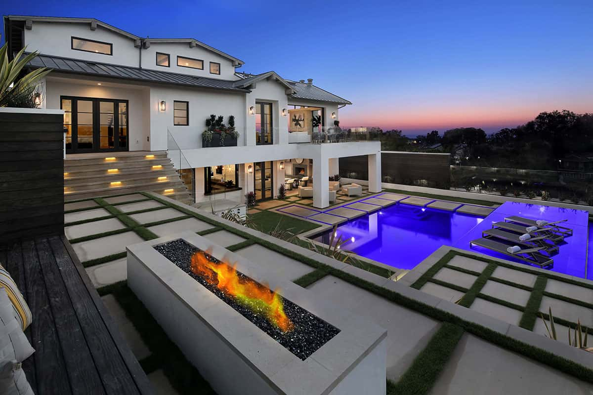 NIght shot of luxury home backyard with pool, fire pit, and gorgeous views.