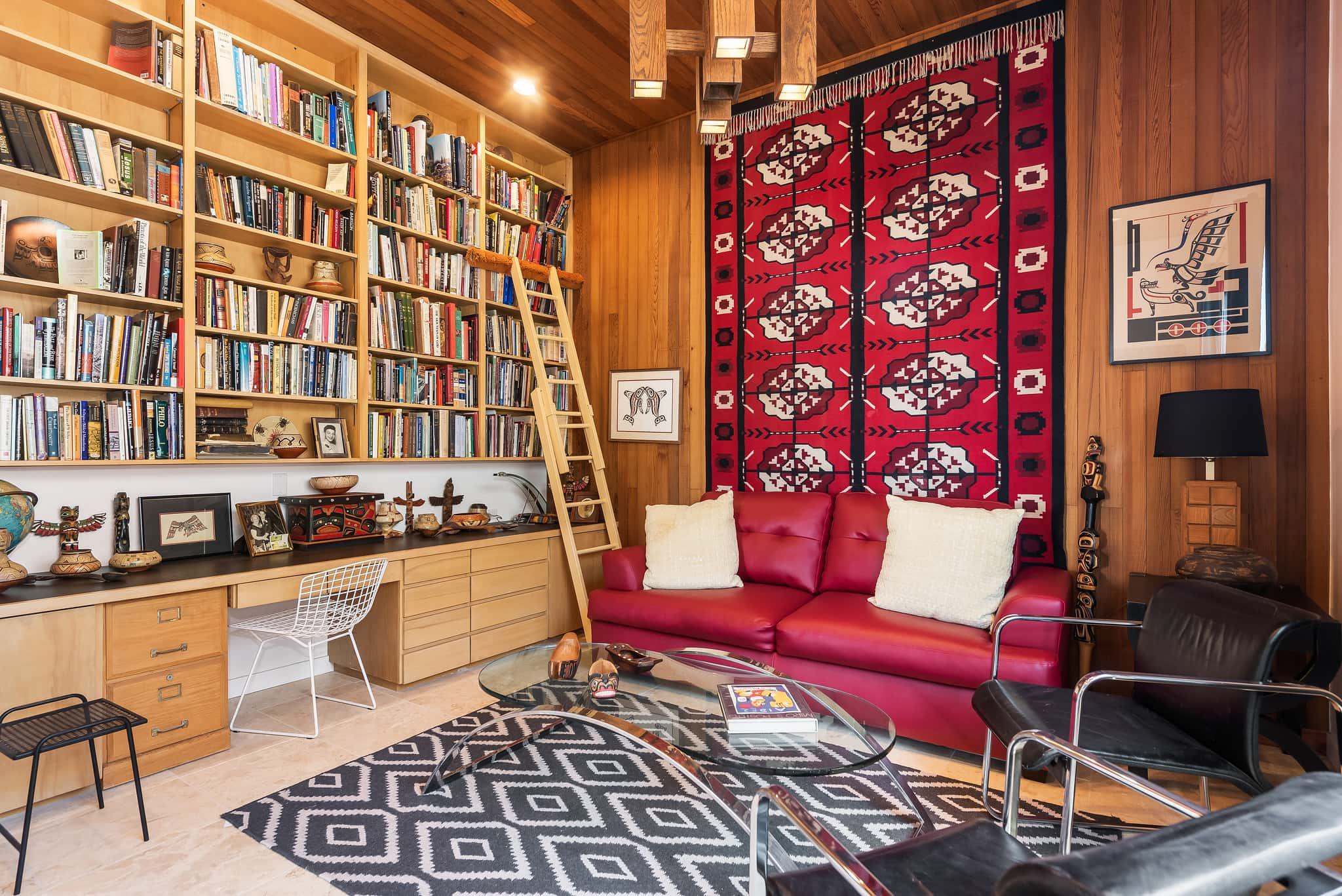 Home library with wall of bookshelves and hanging tapestry.