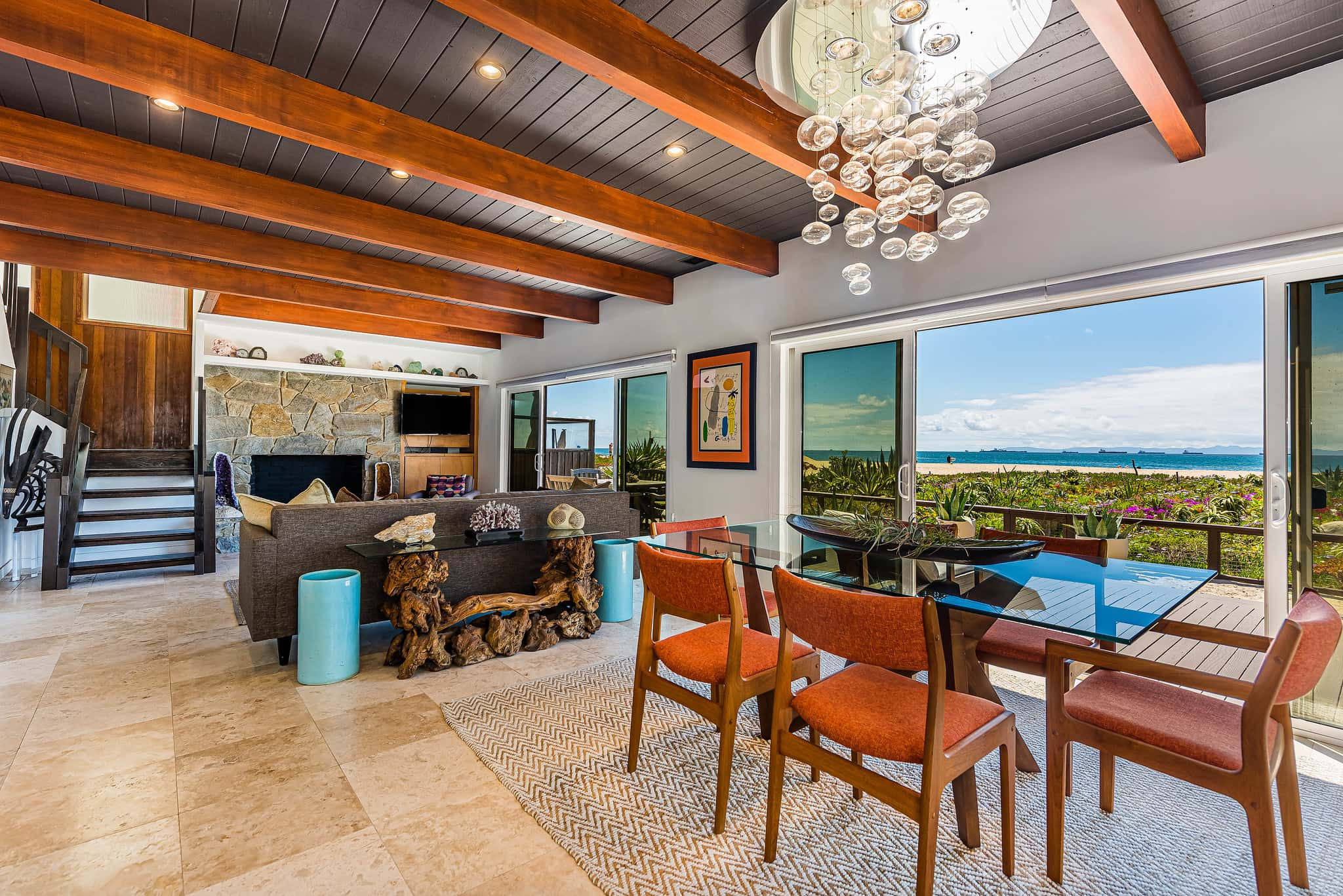 Mid-century modern living room and dining room with sliding doors opening to patio and wood beamed ceilings.