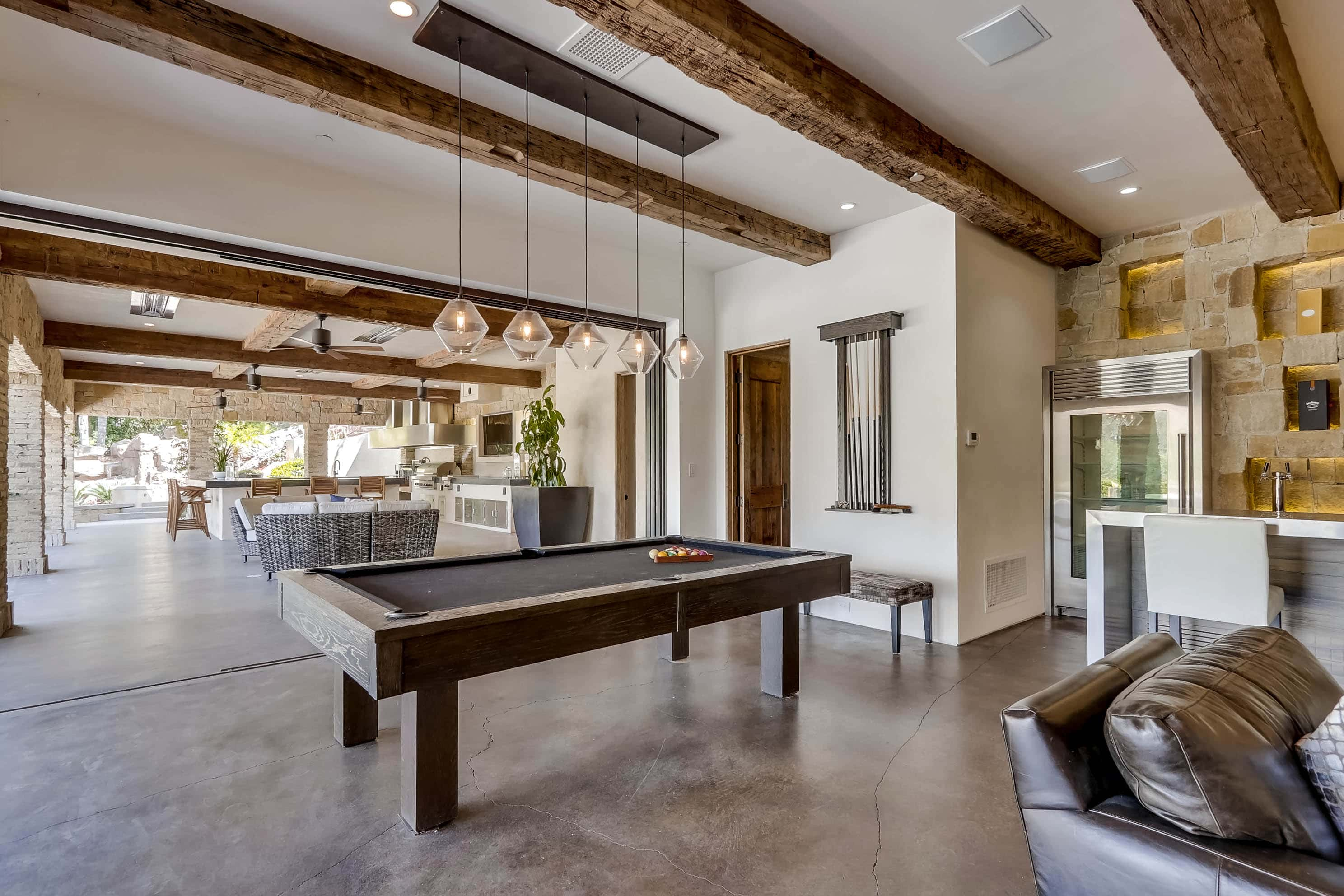 Wood beamed ceilings, retractable walls of glass, pool table, custom lighting, and living room at 22355 Starwood Dr, Yorba Linda