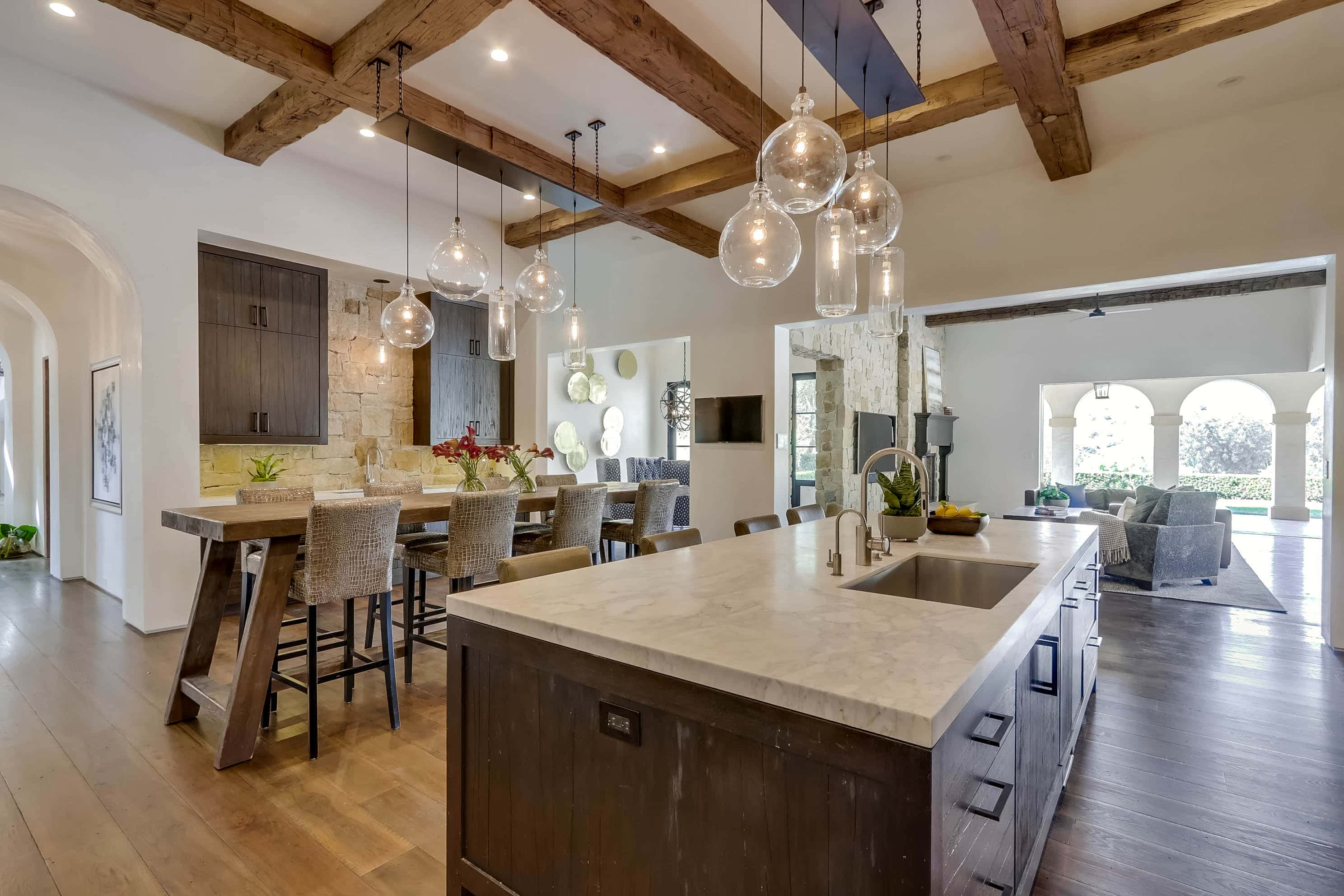 Open layout kitchen and dining room with wood beamed ceilings and retractable walls of glass at 22355 Starwood Drive, Yorba Linda