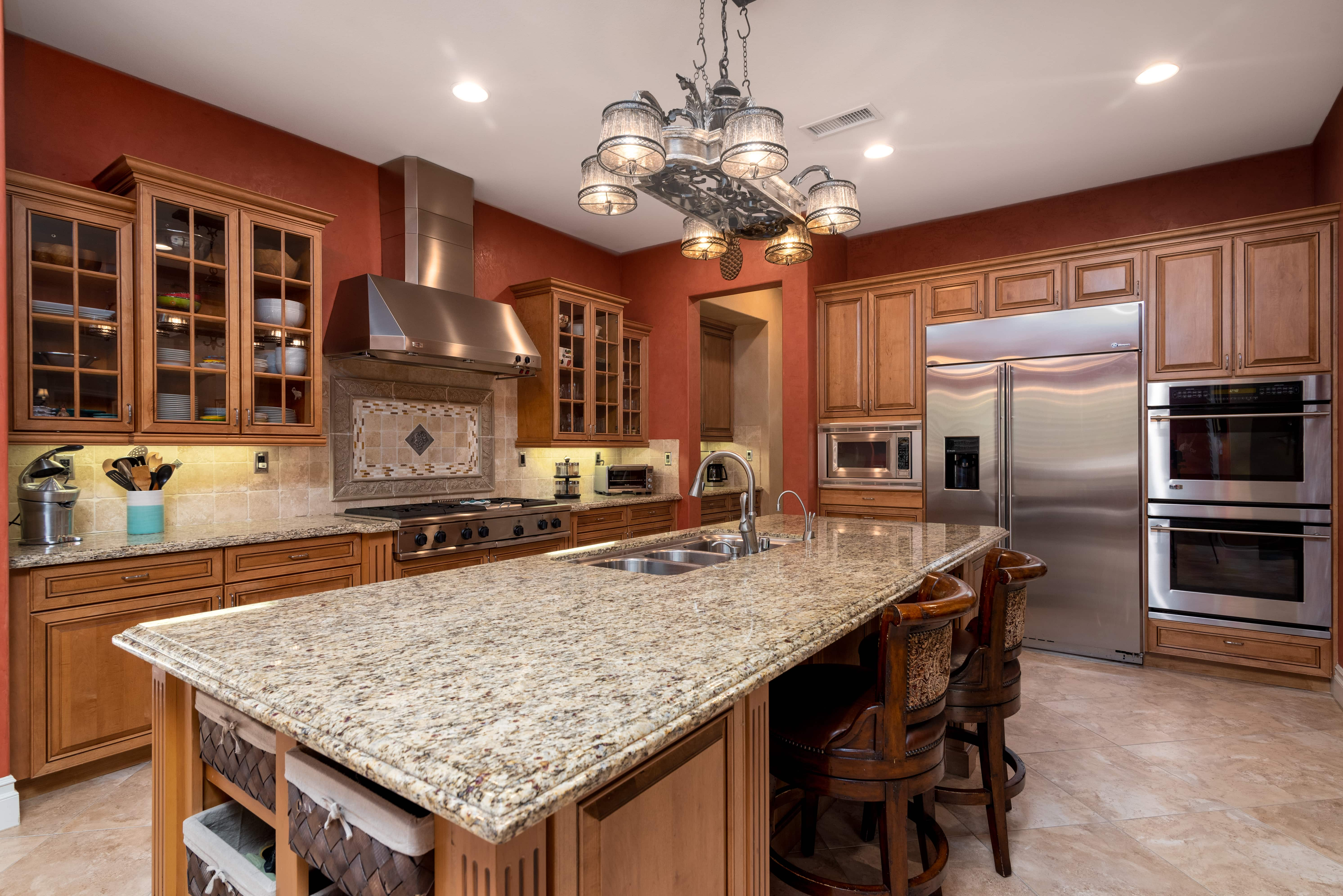 Kitchen with large center island and stainless steel hood range