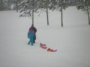 Family enjoys sledding at the Estes Park 18 hole golf course.