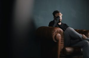 man holding head while sitting on couch