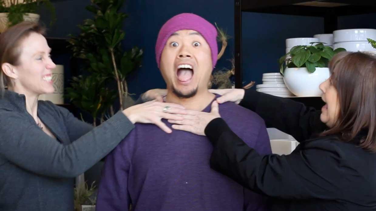 two women pretending to strangle man in hat