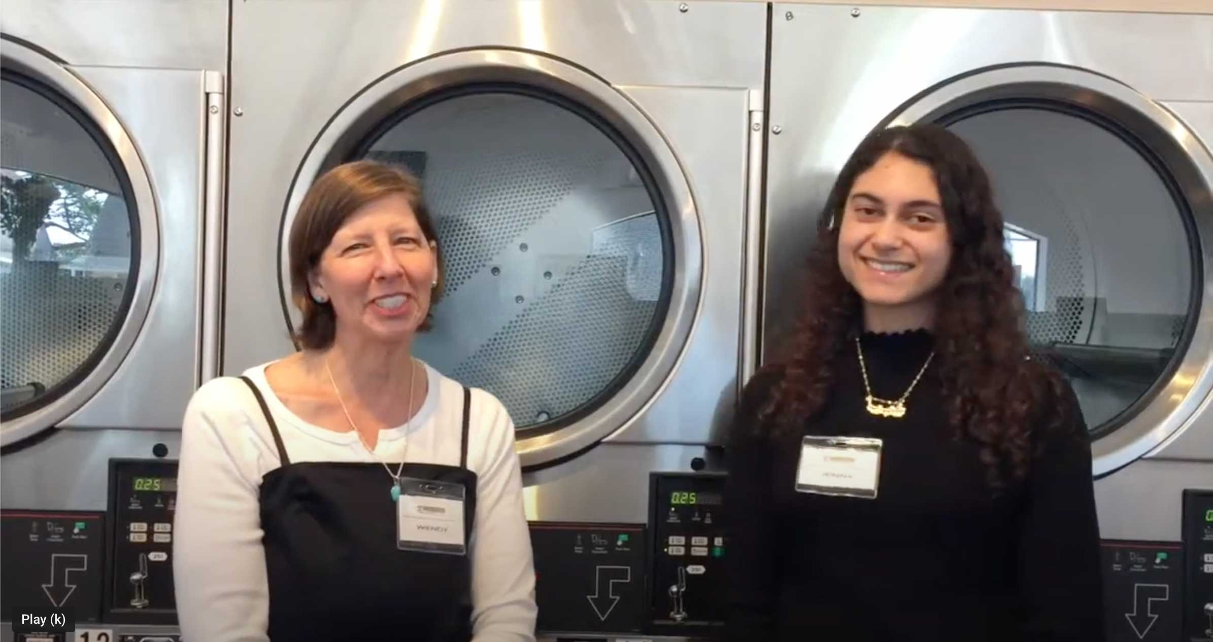two smiling women standing in front of industrial washing machines
