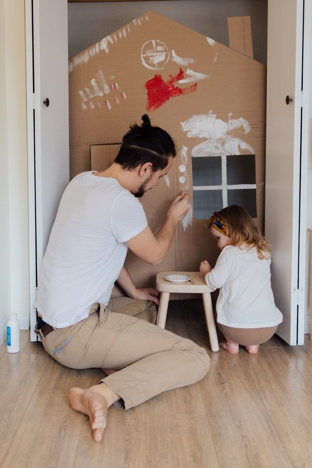 dad and child playing with cardboard house
