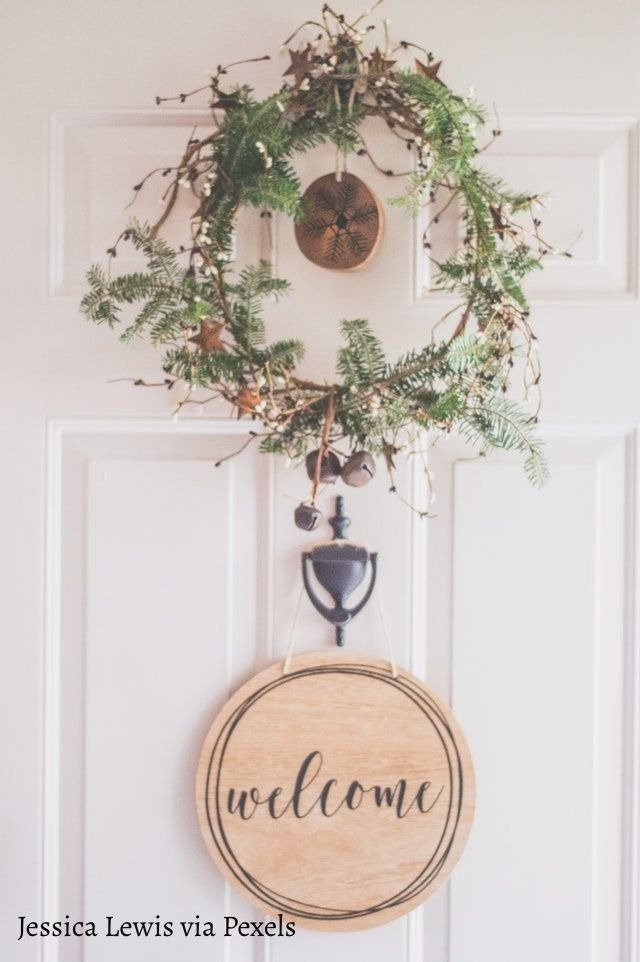 wreath hanging on a door with welcome sign